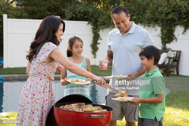 Hispanic mother serving family at backyard barbecue