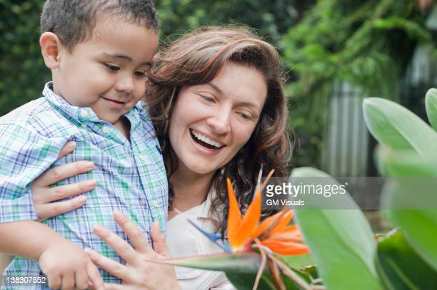 Hispanic mother showing flower to son