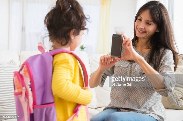 Hispanic mother taking picture of daughter ready for school
