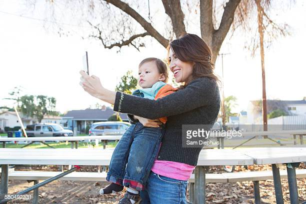 Hispanic mother taking selfie with son in park