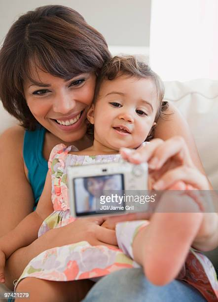 Hispanic mother taking self-portrait with daughter