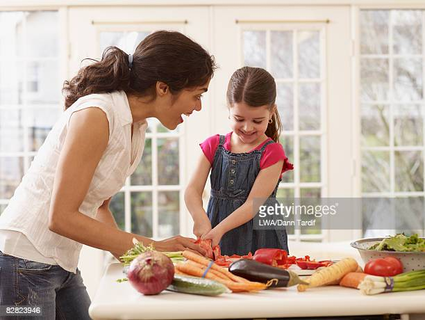 Hispanic mother teaching daughter how to cook