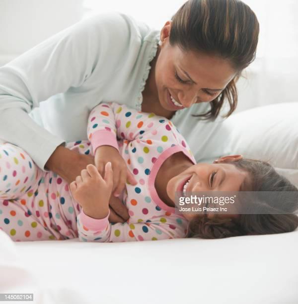Hispanic mother tickling daughter