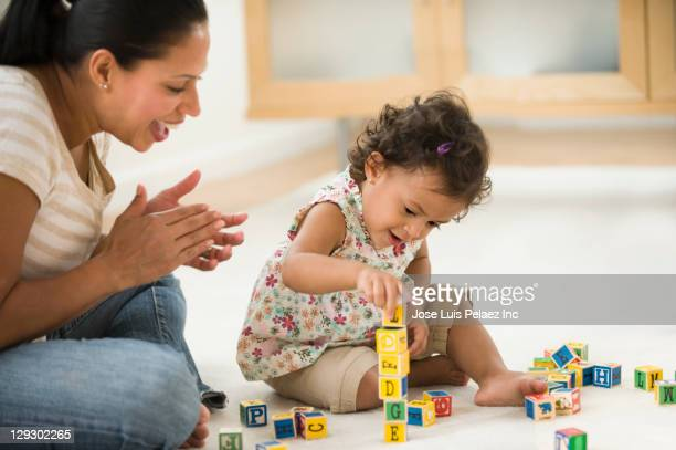 Hispanic mother watching daughter playing with alphabet blocks