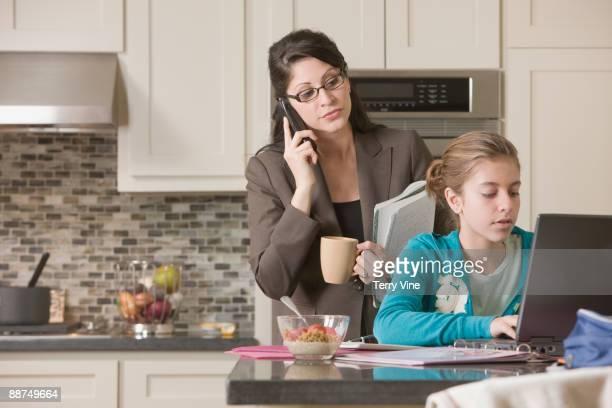 Hispanic mother watching daughter using laptop