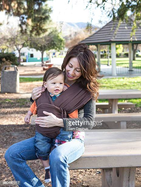 Hispanic mother wearing son in carrier in park