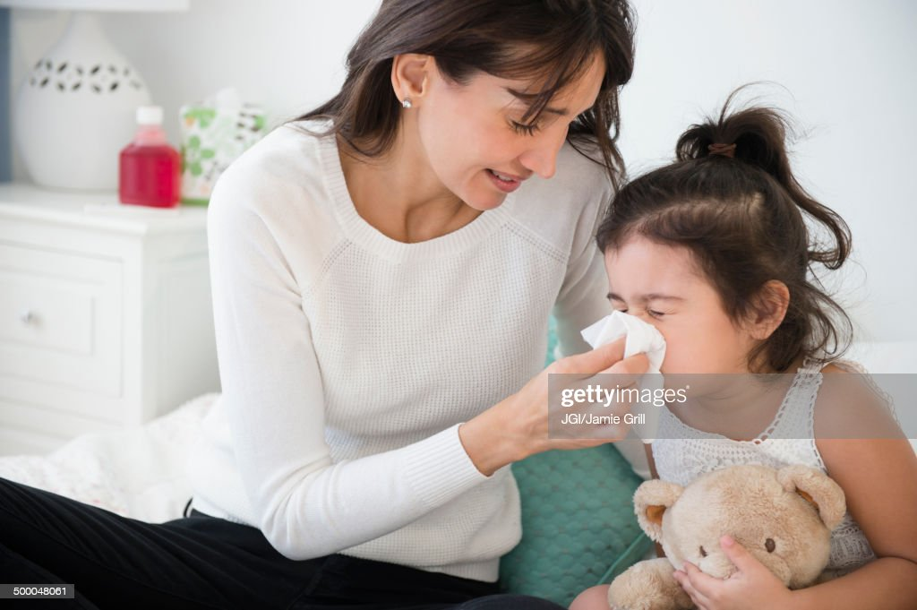 Hispanic mother wiping daughter's nose