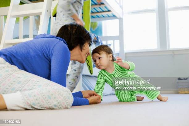 Hispanic mother with toddler in bedroom