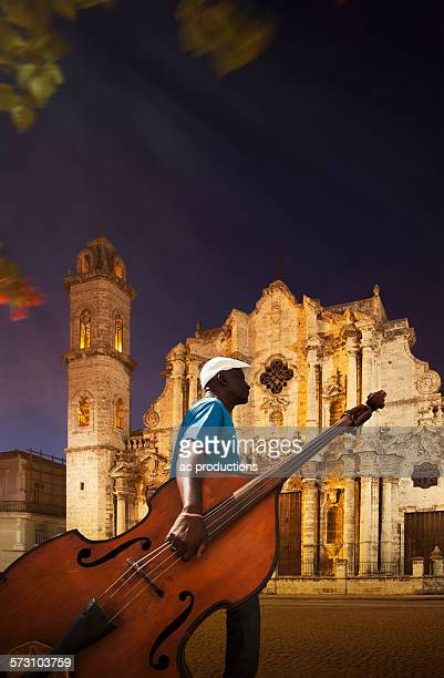 Hispanic musician carrying upright bass near church, Havana, Cuba