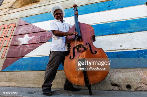 Hispanic musician playing upright bass near Cuban flag, Santiago de Cuba, Santiago, Cuba