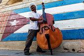 Hispanic musician playing upright bass near Cuban flag, Santiago de Cuba, Santiago, Cuba