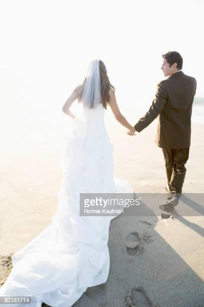 Hispanic newlyweds holding hands