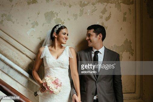 Hispanic newlyweds standing against a grunge wall
