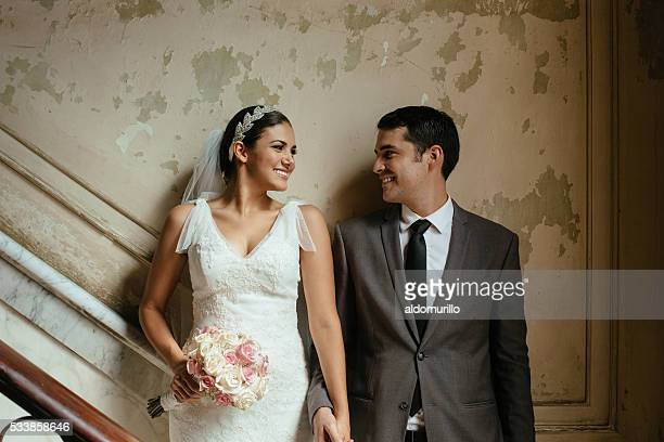 Hispanic newlyweds standing against a grunge wall