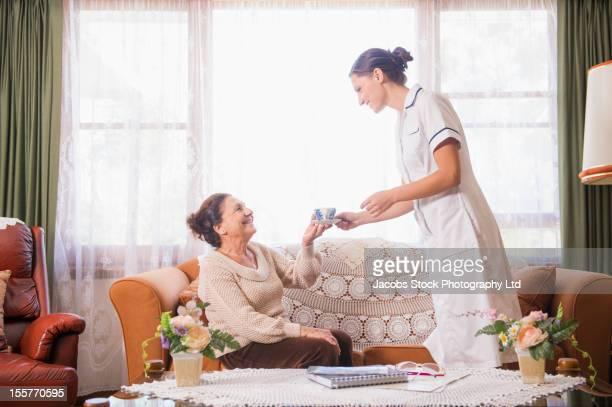 Hispanic nurse handing tea to senior woman