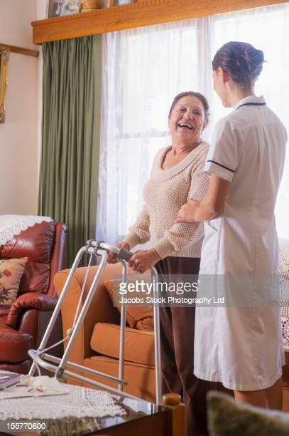 Hispanic nurse helping senior woman