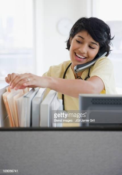 Hispanic nurse talking on telephone