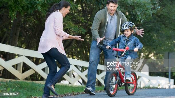 Hispanic parents celebrating son riding bicycle