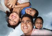 Hispanic parents giving children piggy back rides
