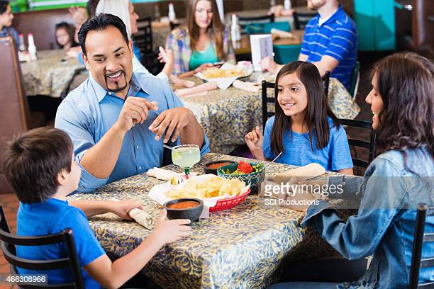 Hispanic parents having dinner in casual Tex-Mex restaurant with kids