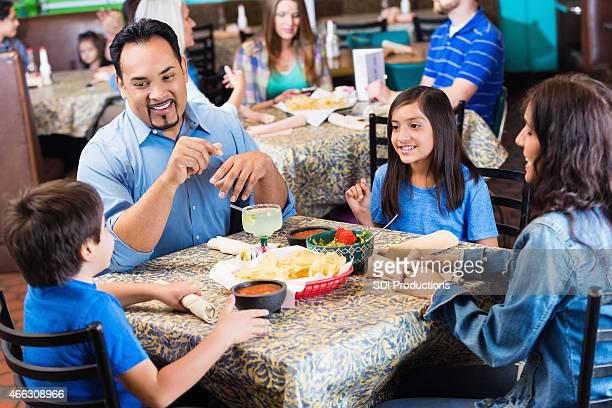 Hispanic parents ayant un dîner au restaurant Tex-Mex décontracté avec les enfants