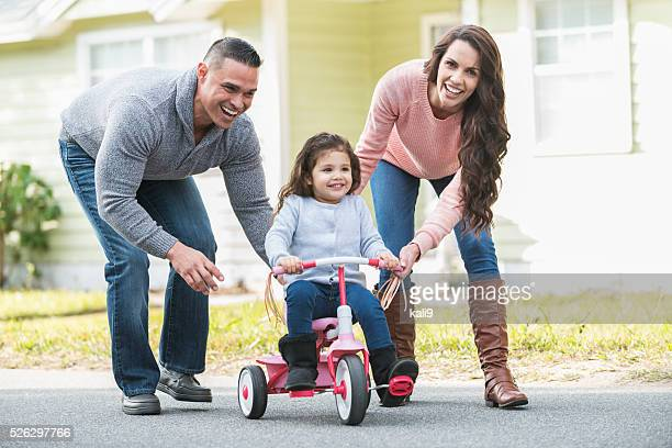 Hispanic parents helping girl ride tricycle