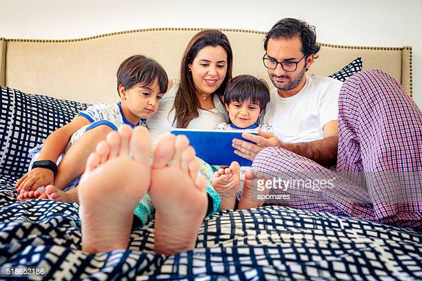 Ispanica genitori utilizzando compressa PC con loro Bambini sul letto