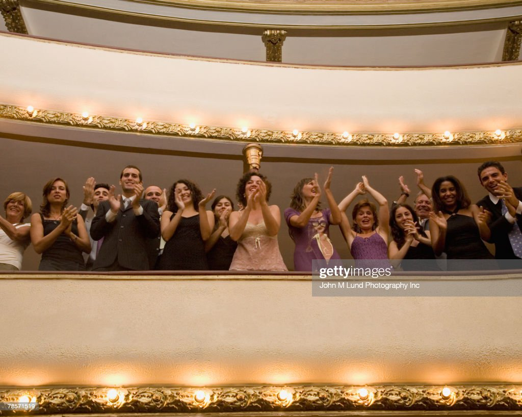 Hispanic people applauding in balcony
