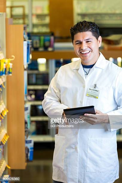 Hispanic pharmacist using digital tablet in pharmacy