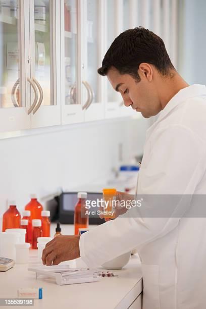 Hispanic pharmacist working in pharmacy