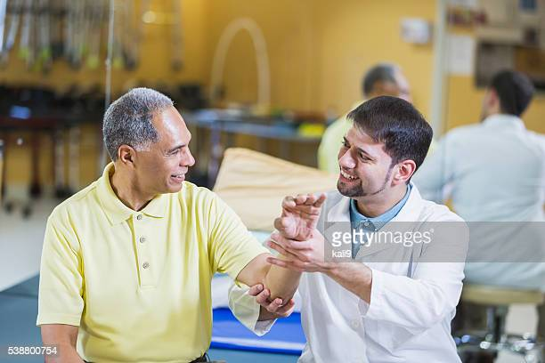 Hispanic physical therapist, African American patient