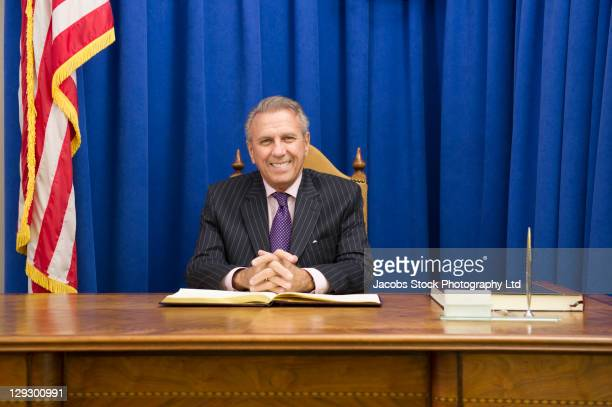 Hispanic politician sitting at desk with American flag
