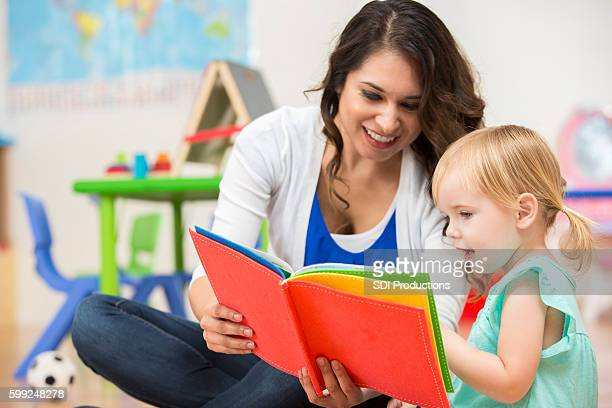 Hispanic preschool teacher reading a book to cute toddler girl