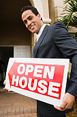 Hispanic real estate agent holding Open House sign