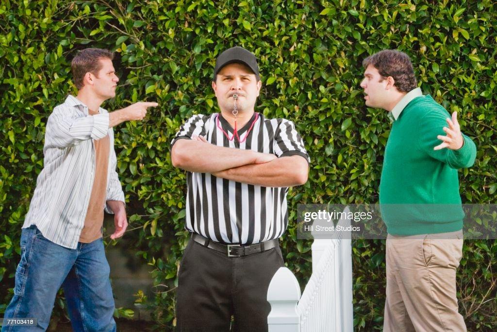Hispanic referee between arguing neighbors