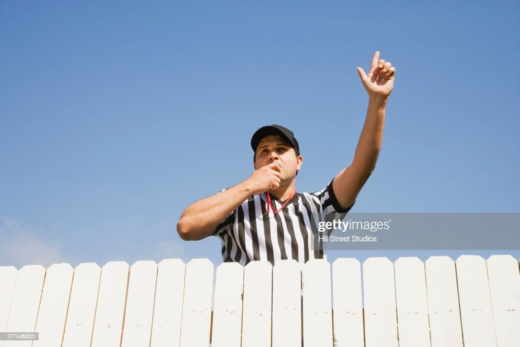 Hispanic referee blowing whistle over fence : Stock Photo
