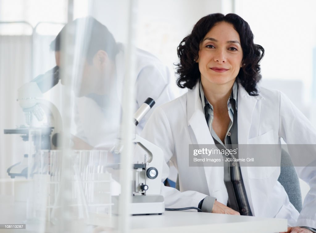 Hispanic researcher in laboratory next to microscope : Stock Photo