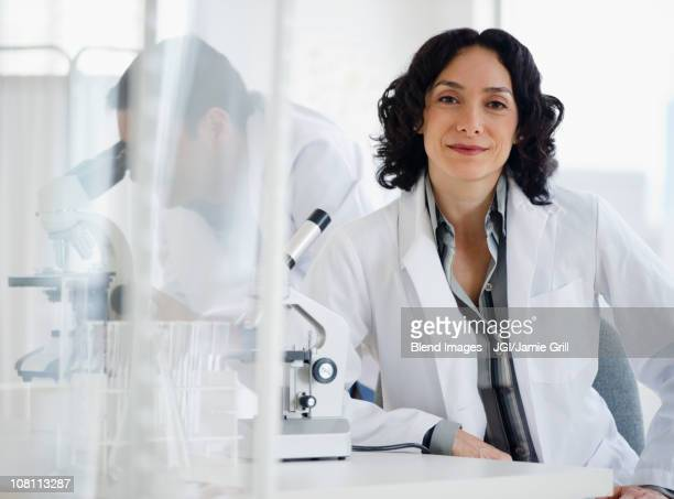 Hispanic researcher in laboratory next to microscope