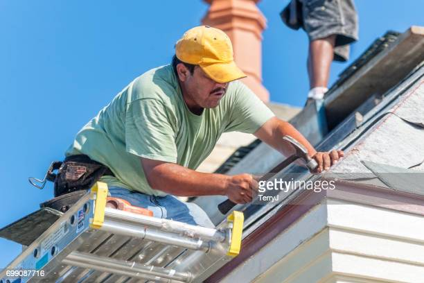 Hispanic Roofer Hammers a Copper Nail into a Piece of Slate Tile on the Roof