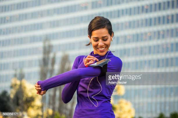 Hispanic runner using cell phone near high rise building