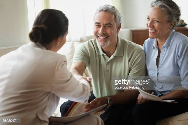 Hispanic saleswoman talking to clients in living room