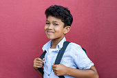 Young hispanic school boy ready with backpack to go to elementary school. Portrait of happy middle eastern schoolboy standing against red background. Indian child looking at camera isolated with copy