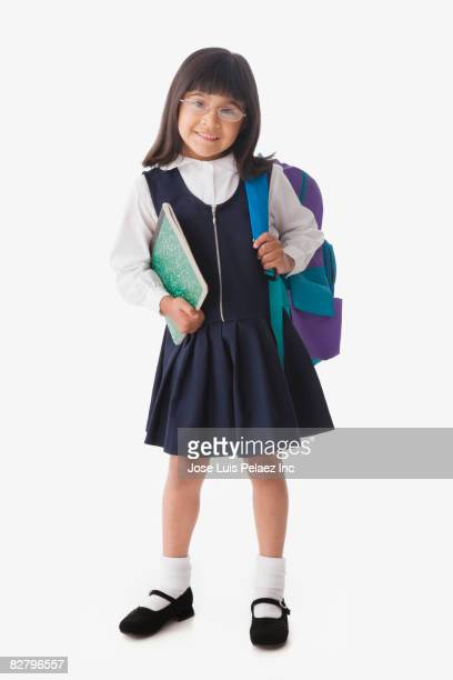 Hispanic school girl holding backpack and notebook