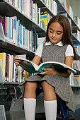 Hispanic school girl reading library book