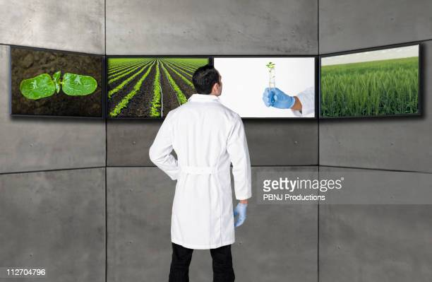 Hispanic scientist looking at images on television screens