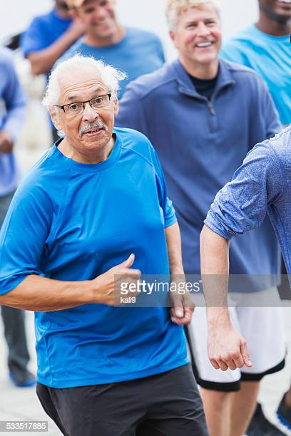 Hispanic senior man running with group