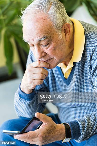 Hispanic senior man using his smart phone