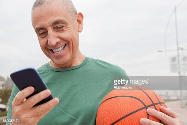 Hispanic senior man with basketball using cell phone