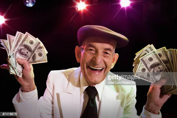 Hispanic senior man with cash in nightclub