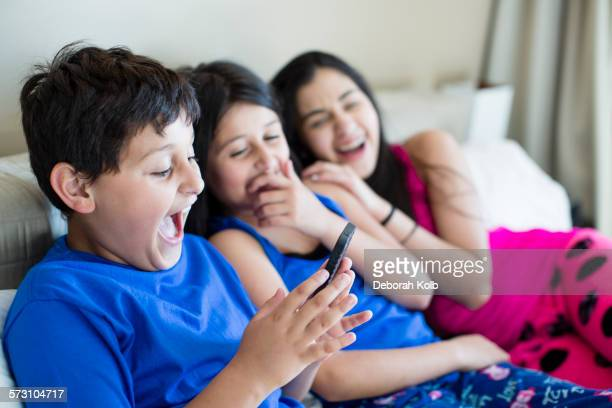 Hispanic siblings using cell phone on sofa